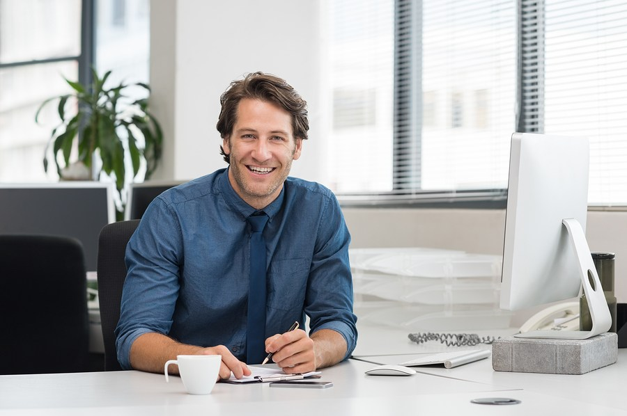 Cheerful young businessman working at desk in office. Successful business man sitting in office with a cup of coffee. Portrait of happy young businessman laughing and looking at camera.